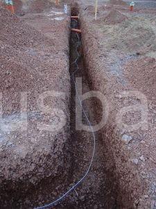Das Stahlband ist der Fundamenterder. Er ist an den Metallbögen befestigt, damit er nicht auf dem Erdboden liegt. Damit soll verhindert werden, dass er Feuchtigkeit ausgesetzt wird und anfängt zu rosten. Das Metallband sollte auch nicht flach verlaufen, damit der Beton das Band vollständig umschließen kann und sich darunter keine Luftblasen bilden können.
