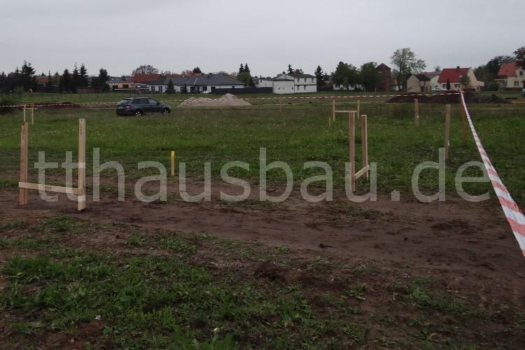 Hier erkennt man, wie unser Grundstück bisher als Fahrspur genutzt wurde. Jetzt stehen dort Schnurböcke. Der eine gelbe Pfosten markiert eine Hausecke.